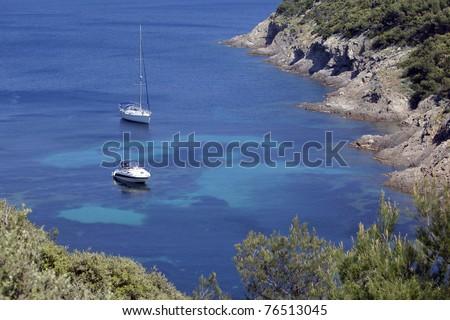 Boats anchored near an island coast in mediterranean sea. Port Cros national park, France - stock photo