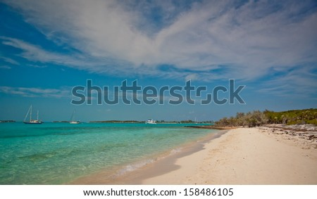 Boats anchored off a beautiful island in the Bahamas.  copy space available on the white sand beaches, turquiose waters or blue sky - stock photo