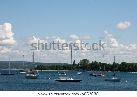 Boats anchored off the shore of Lake Michigan in Petoskey. A hot, humid northern afternoon. - stock photo