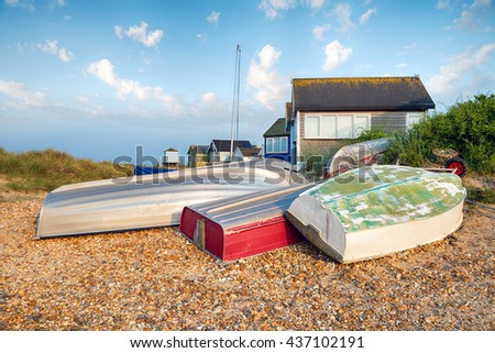 Boats and beach huts at Mudeford Spit at Christchurch on the Dorset coast - stock photo