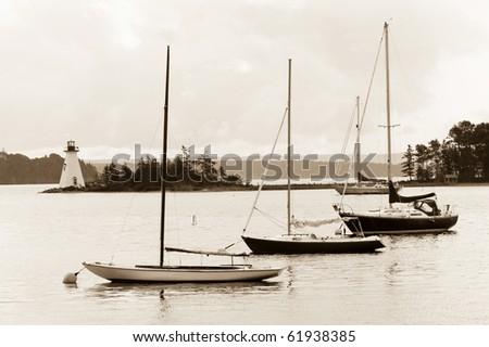 Boats and lighthouse on Bras D'Or lake, Cape Breton, Nova Scotia - stock photo