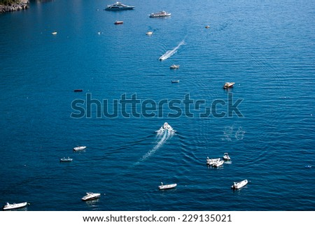 Boats and speedboats parked offshore