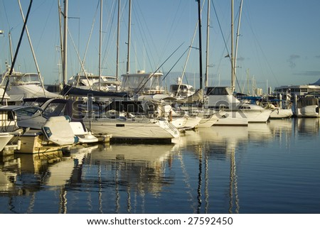 Boats and yachts lined up at the marina in the early morning golden light. - stock photo