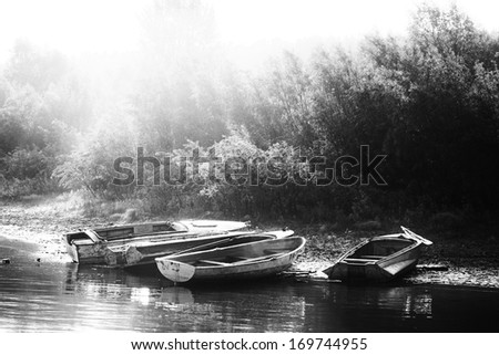 boats ashore. black & white morning landscape with sunrays