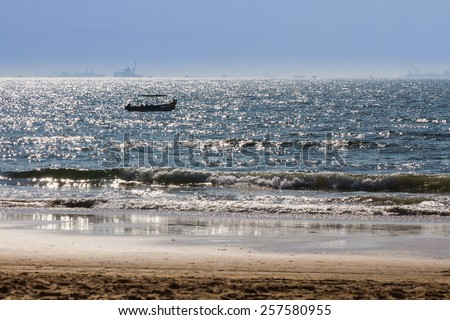 Boats at Arabian sea. Cargo ships on the background. View from beach in Goa, India