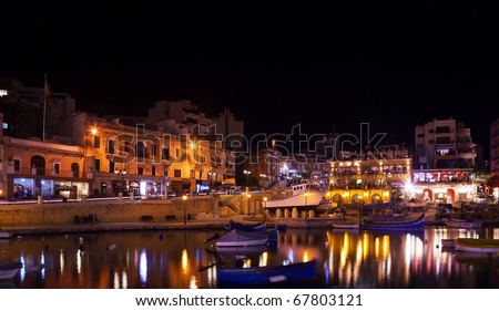 Boats at quay in St. Julian's bay in night. Malta