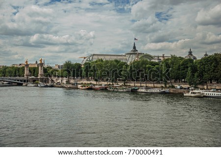 "Boats at Seine River, Alexandre III bridge and Grand Palais building in the background in Paris. Known as the ""City of Light"", is one of the most impressive world's cultural center. Northern France."