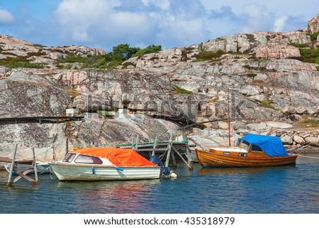 Boats at the jetty on a rocky coastline - stock photo