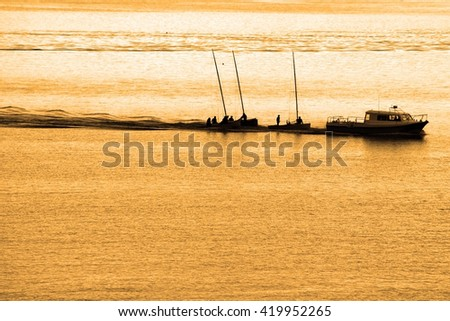 boats being towed in cobh ireland at sunset - stock photo