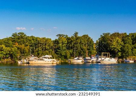 Boats docked in the Back River, seen at Cox Point Park, in Essex, Maryland. - stock photo