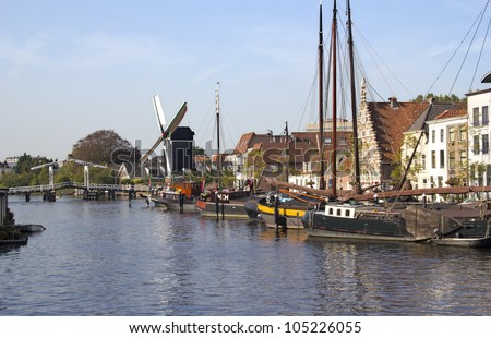 Boats, drawbridge and windmill along a canal in Leiden, Holland - stock photo