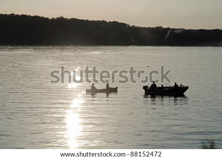 boats fishing on a lake at sunset - stock photo