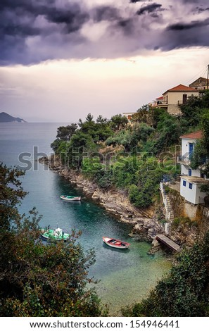 Boats in a gulf in Ithaca island, Greece, at dusk, under a cloudy sky - stock photo