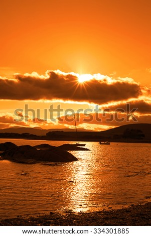 boats in a quiet bay near kenmare on the wild atlantic way ireland with an orange sunset - stock photo
