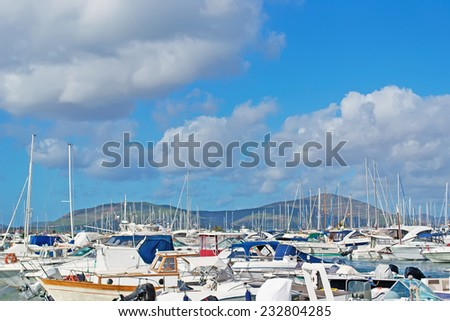 boats in Alghero harbor on a cloudy day - stock photo