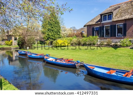 Boats in canal in Giethoorn, a village in the Netherlands. Part of the village has no roads and some houses are accessible by boat only.