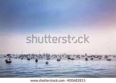 Boats in Mumbai Harbor at blue sky, Maharashtra, India - stock photo