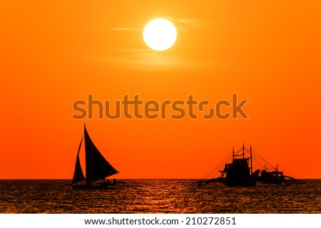 Boats in silhouette against a colorful tropical sunset - stock photo