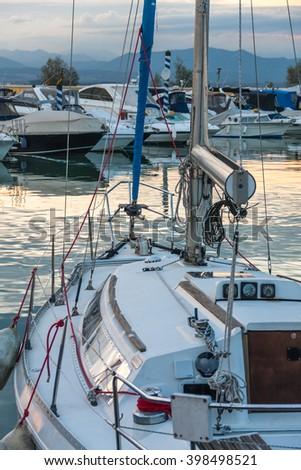 Boats  in the harbor on Lake Garda.  Lots of boats docked to coast. Boats in port. Moored boats. Landscape of boats. Blue sky and fishing boats. Beautiful boats at coast. - stock photo