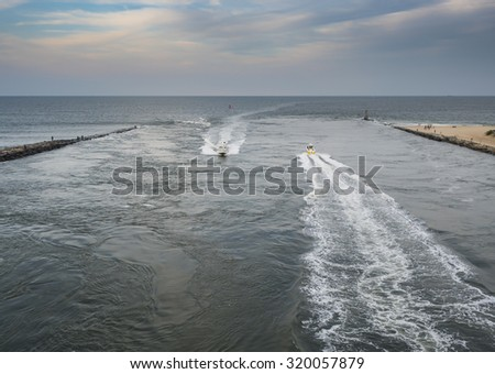 Boats in the Indian River inlet in Delaware at sunset. - stock photo