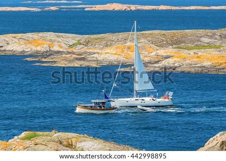 Boats in the rocky coastal scenery - stock photo