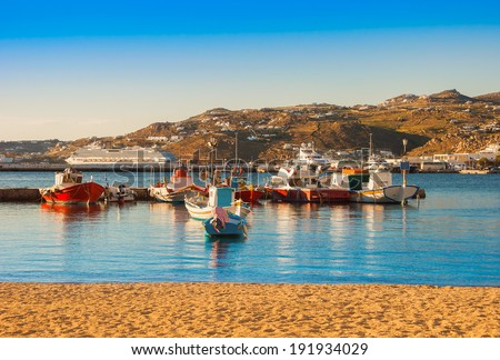 Boats in the sea bay near the town of Mykonos in Greece against the sky - stock photo