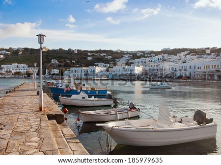 Boats in the sea bay near the town of Mykonos in Greece against the sky with clouds - stock photo