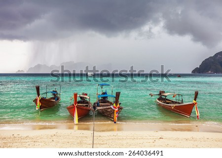 Boats in the tropical sea under gloomy dramatic sky. Thailand  - stock photo