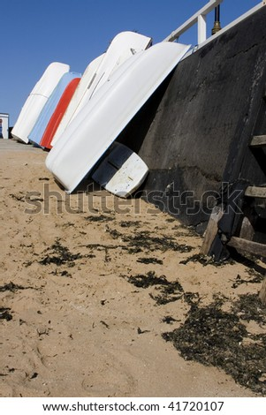Boats leaning up on harbour wall, Broadstairs - stock photo