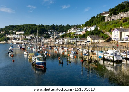 Boats Looe harbour and river Cornwall England, with blue sea on a sunny summer day and town on the hillside - stock photo