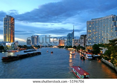Boats make their way along the Chao Phraya River at dusk