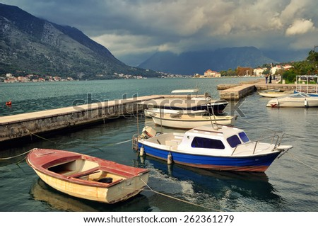 Boats moored in Dobrota - small town in Kotor Bay, Montenegro with Mountains - stock photo