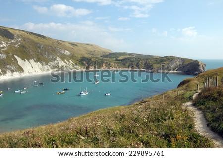 Boats moored in Lulworth Cove on Dorset coast - stock photo