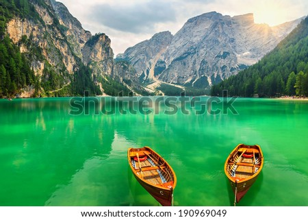 Boats on a mountain lake and sunshine in the Dolomite Alps,Sudtirol,Italy,Europe - stock photo
