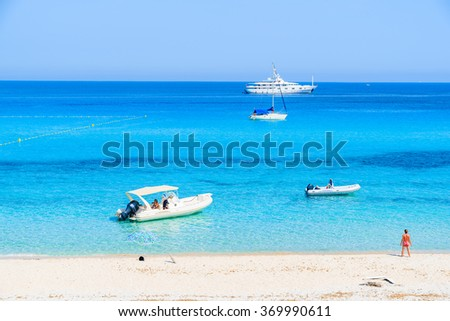 Boats on azure sea and young woman standing on Saleccia beach , Corsica island, France - stock photo