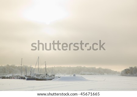 Boats on dock in winter, Finland - stock photo