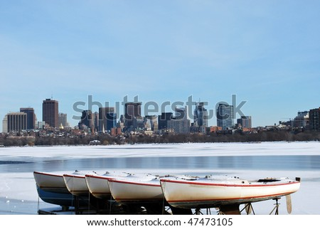 boats on frozen charles river overlooking boston skyline in the winter