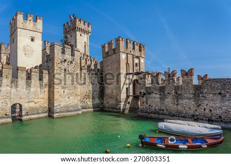 Boats on Lake Garda and medieval fortification in Sirmione, Italy. - stock photo