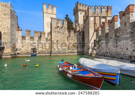 Boats on lake Garda and Scaliger medieval castle in town of Sirmione, Italy. - stock photo