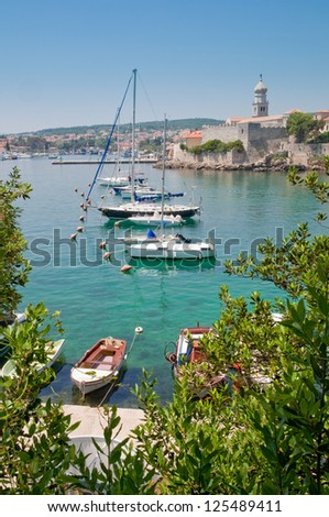 Boats on little port beside Krk old town view with vegetation - Croatia - stock photo