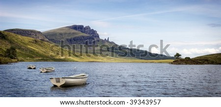 Boats on Loch Fada with Old Man of Storr in the background on Isle of Skye, Scotland - stock photo