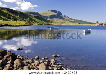 Boats on Loch leathann with the old man of storr in the background - stock photo