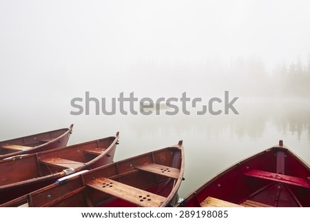 Boats on the lake at morning fog. - stock photo