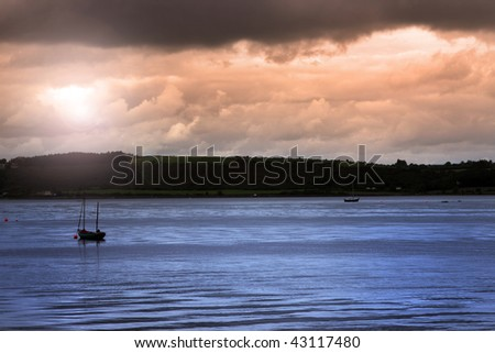 boats on the river edge in youghal a beautiful irish town on the coast - stock photo