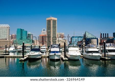 Boats on the water of Baltimore, Maryland's Inner Harbor with city buildings in the background against a clear blue sky - stock photo