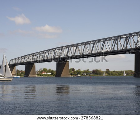 Boats on water and bridge with bridge-walking bridge and small people in gray coveralls on top of the Old Little Belt Bridge. - stock photo