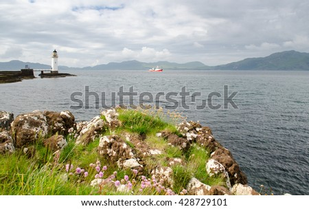 Boats pass the lighthouse at Rubha nan Gall on the rocky shore of Scotland's Isle of Mull. - stock photo