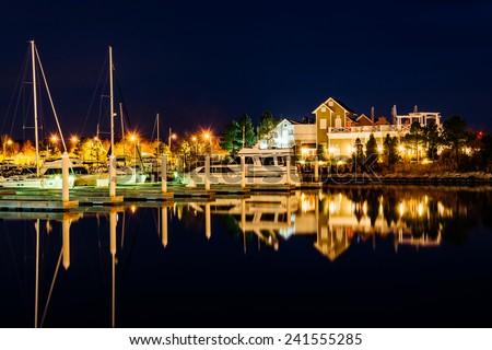 Boats reflecting at night at the Bay Bridge Marina in Kent Island, Maryland. - stock photo