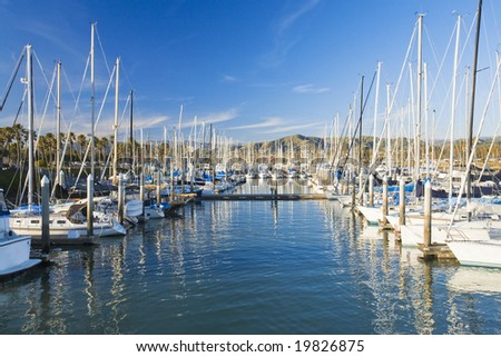 Boats rest in a harbor with mountains in the background. - stock photo