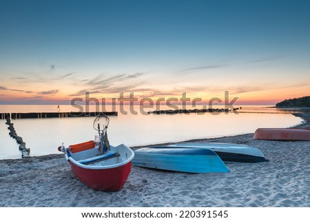 Boats resting on sandy beach in the evening - stock photo